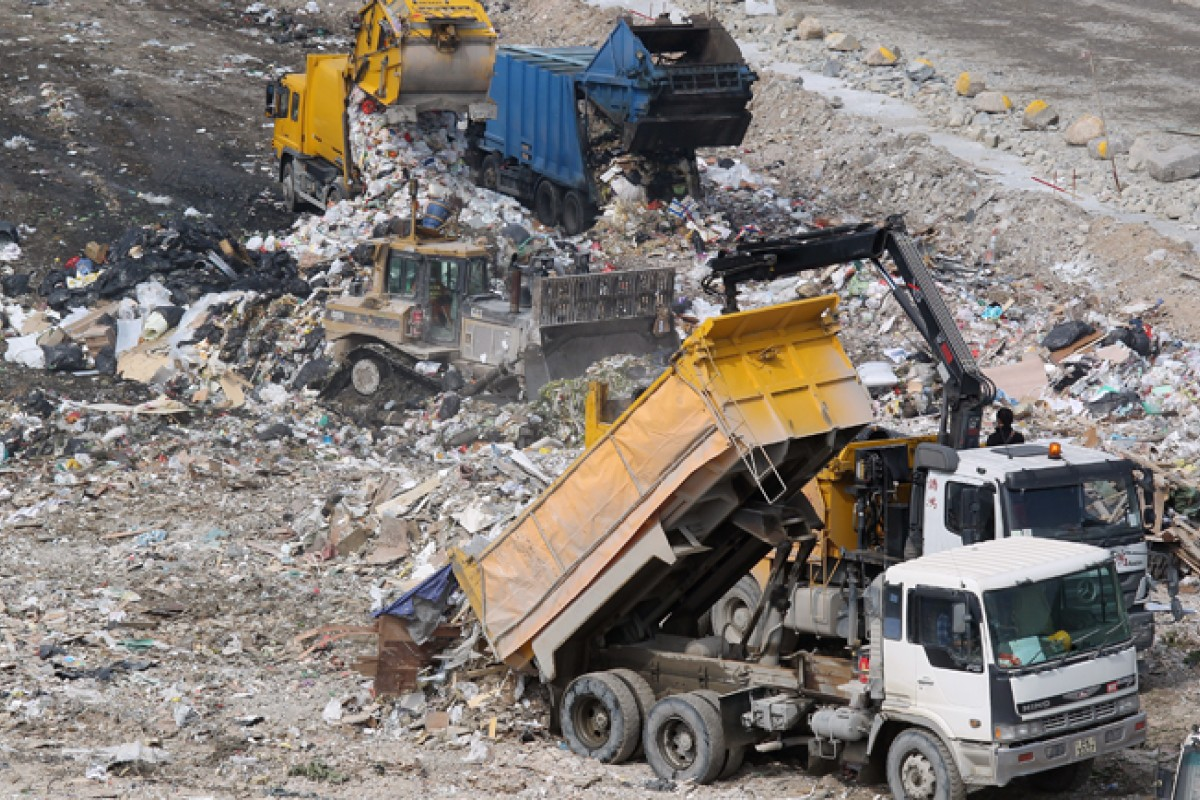 A truck unloads waste into the landfill.