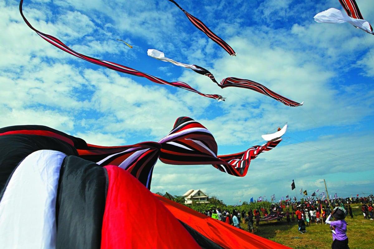 Traditional black, red and white kites take to the skies at the Bali Kite Festival in Pantai Padang Galak, Sanur.