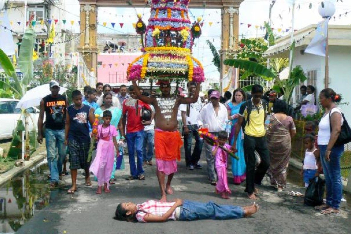 A penitent lies in front of a procession.
