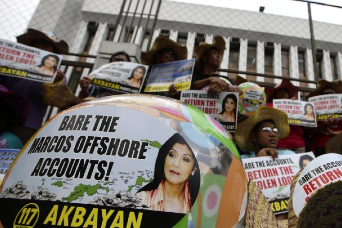 Protesters holding banners bearing the face of Ferdinand and Imelda Marcos' daughter Imee demand action on the former first family's offshore accounts during a protest in Manila on April 8. Photos: AFP; AP; Reuters