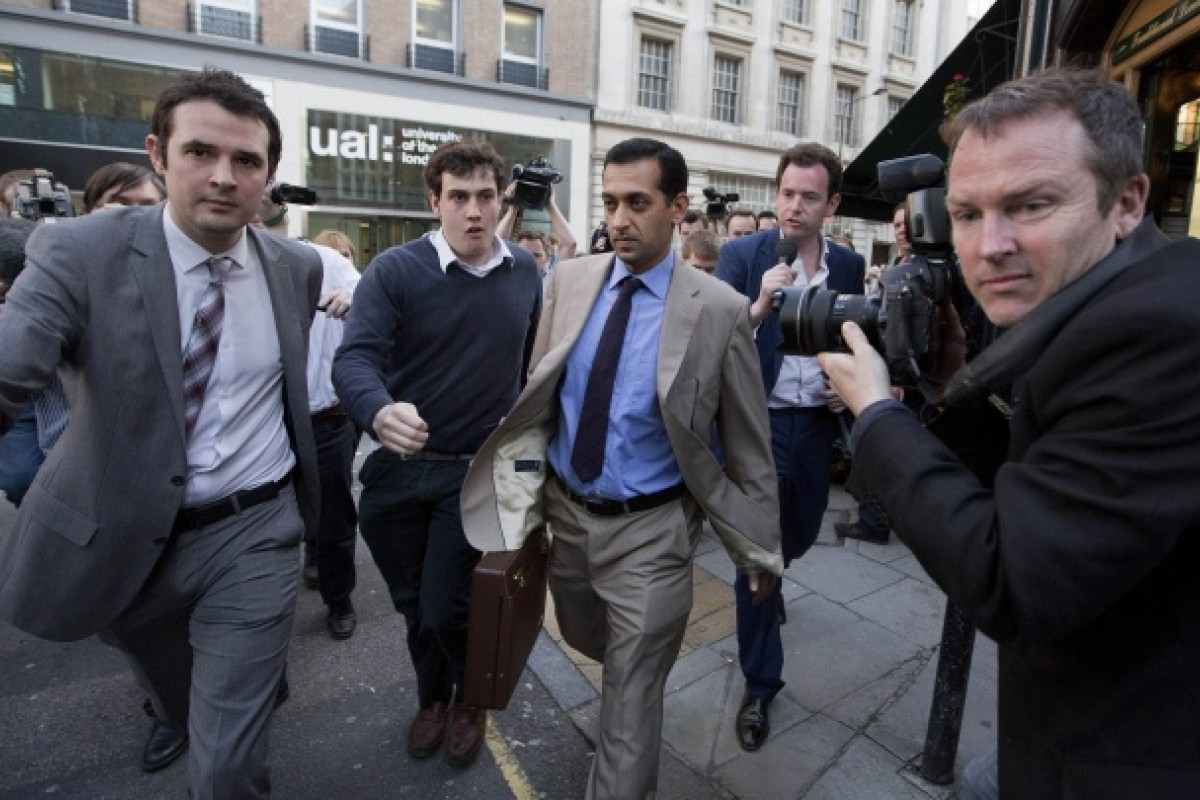 Horse trainer of the leading Godolphin stable Mahmood Al Zarooni (C) is followed by reporters as he leaves a disciplinary hearing at the British Horseracing Authority. Photo: AFP