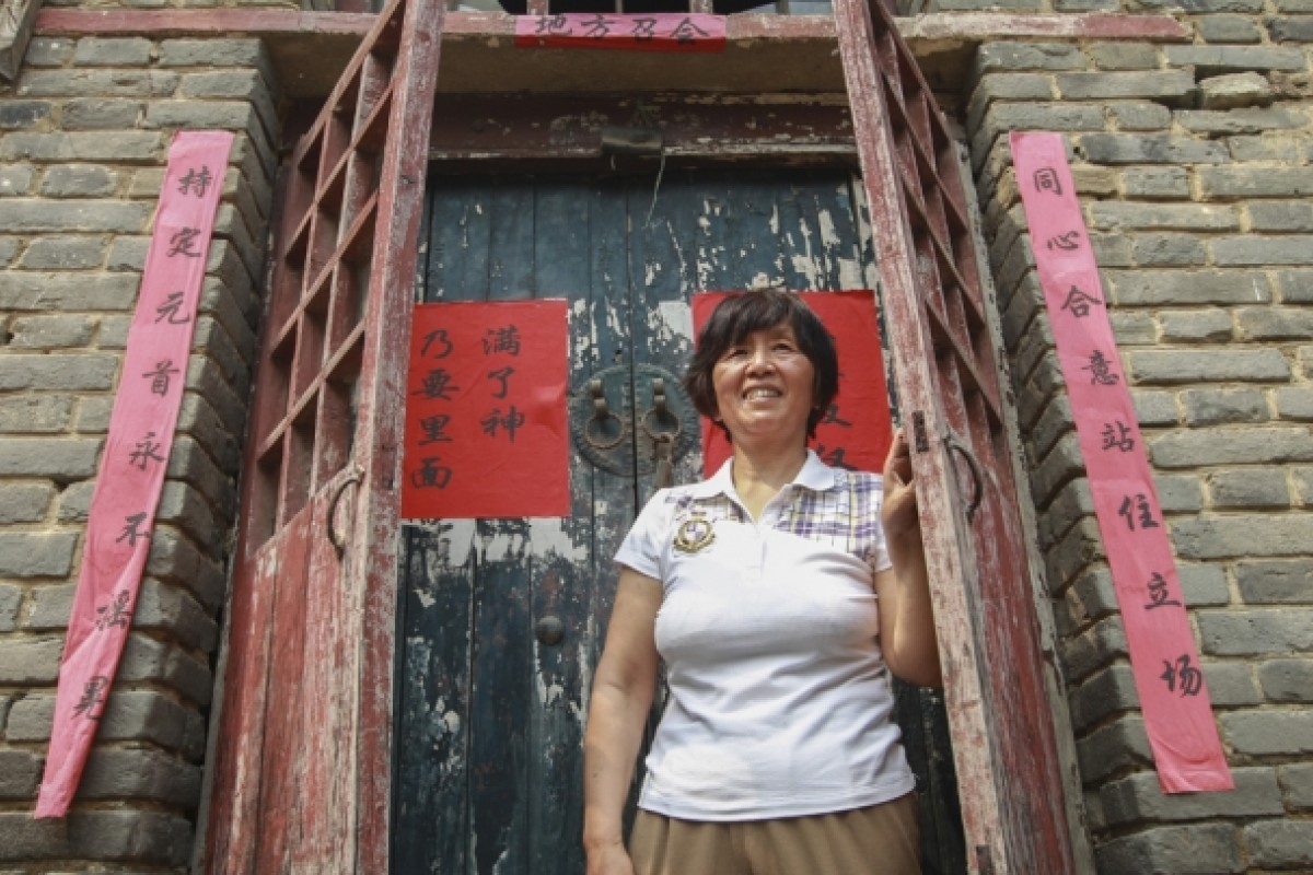 Bai Jiuni, whose husband has been jailed for his alleged involvement with ''evil cult'' The Shouters, in front of their family home in Ye county, Henan province.