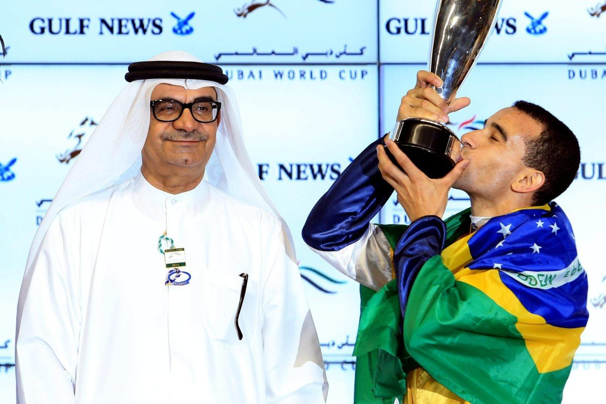 Joao Moreira, draped in his native Brazilian flag, kisses his trophy after winning the Golden Shaheen.