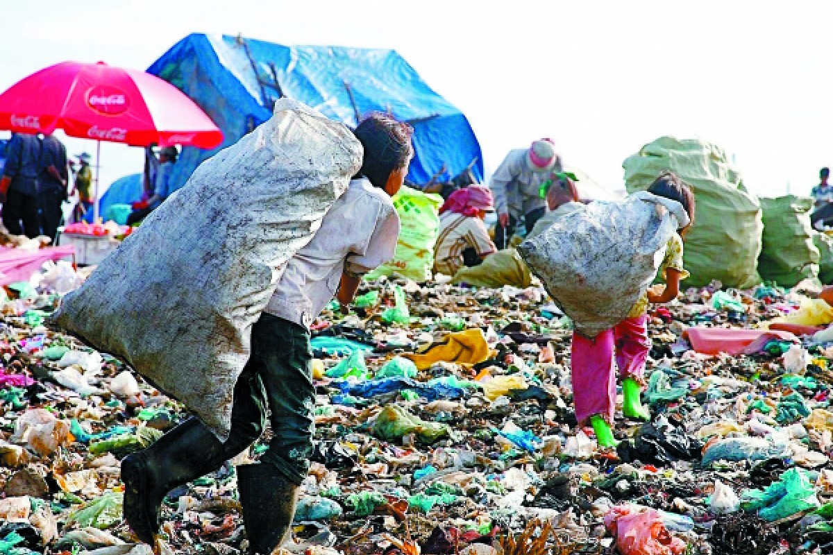 A photo from just a few years ago shows Ang Srey Mom (left) in her former life, hauling a bag of rubbish at the dump in Stung Meanchey.