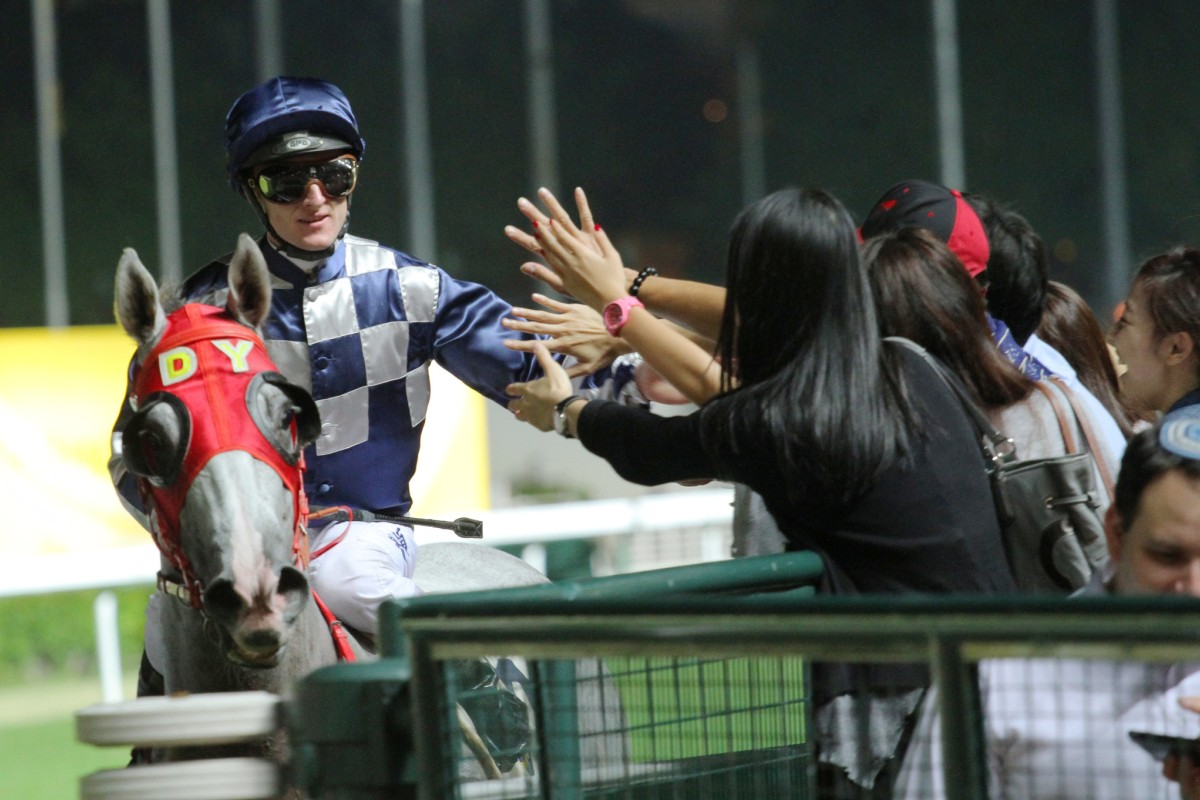 Zac Purton high-fives adoring fans after winning the Ireland Trophy with Choice Treasure. Photo: Kenneth Chan
