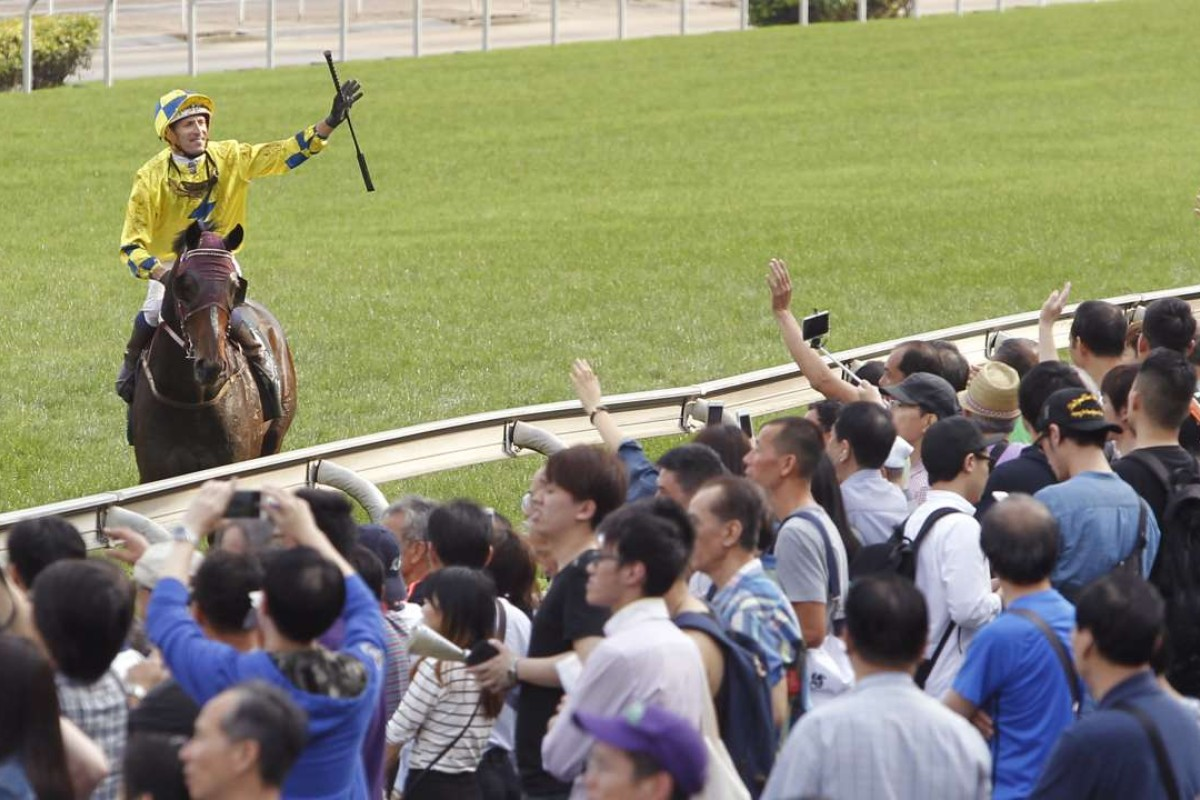 Hugh Bowman salutes the crowd after winning the QE II Cup on Werther. Photos: Kenneth Chan