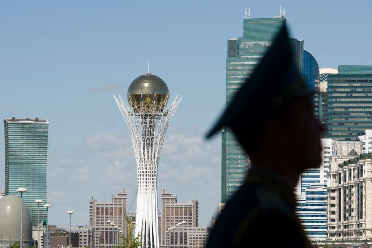 The Byterek tower is visible in the centre of Astana as a soldier stands guard outside the Presidential Palace. Photo: AFP
