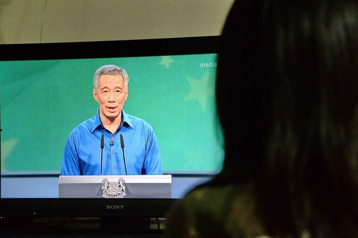 A Singaporean resident watches a live televised speech by Prime Minister Lee Hsien Loong after he became ill during a National Day Rally on August 21, 2016. Photo: AFP