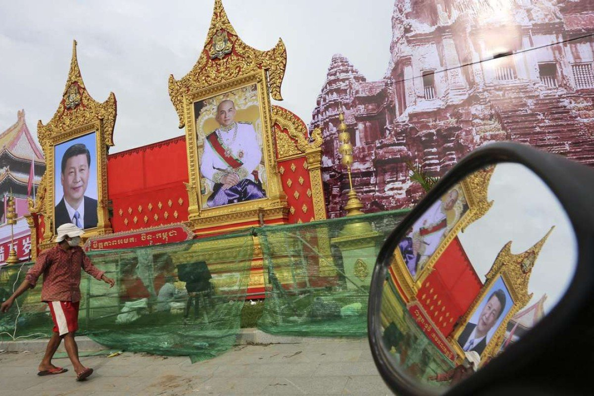 A Cambodian passes portraits of Chinese President Xi Jinping and Cambodian King Norodom Sihamoni in Phnom Penh, Cambodia ahead of Xi's visit. Photo: EPA