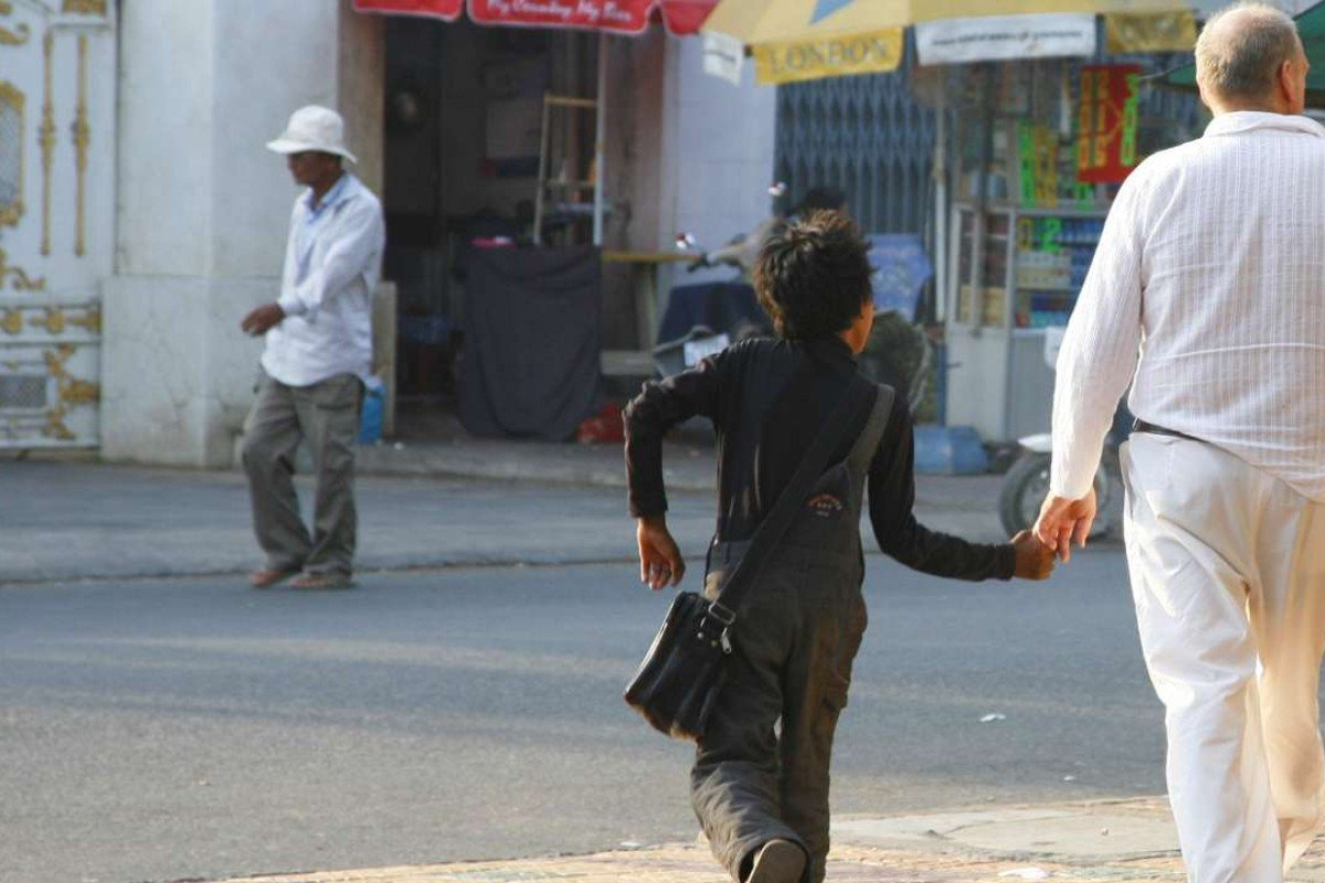 A middle-aged Western man walks hand in hand with a local boy in Phnom Penh. A report of this kind of suspicious behaviour is usually enough to convince Action Pour Les Enfants to begin an investigation. Photo: Courtesy of APLE Cambodia