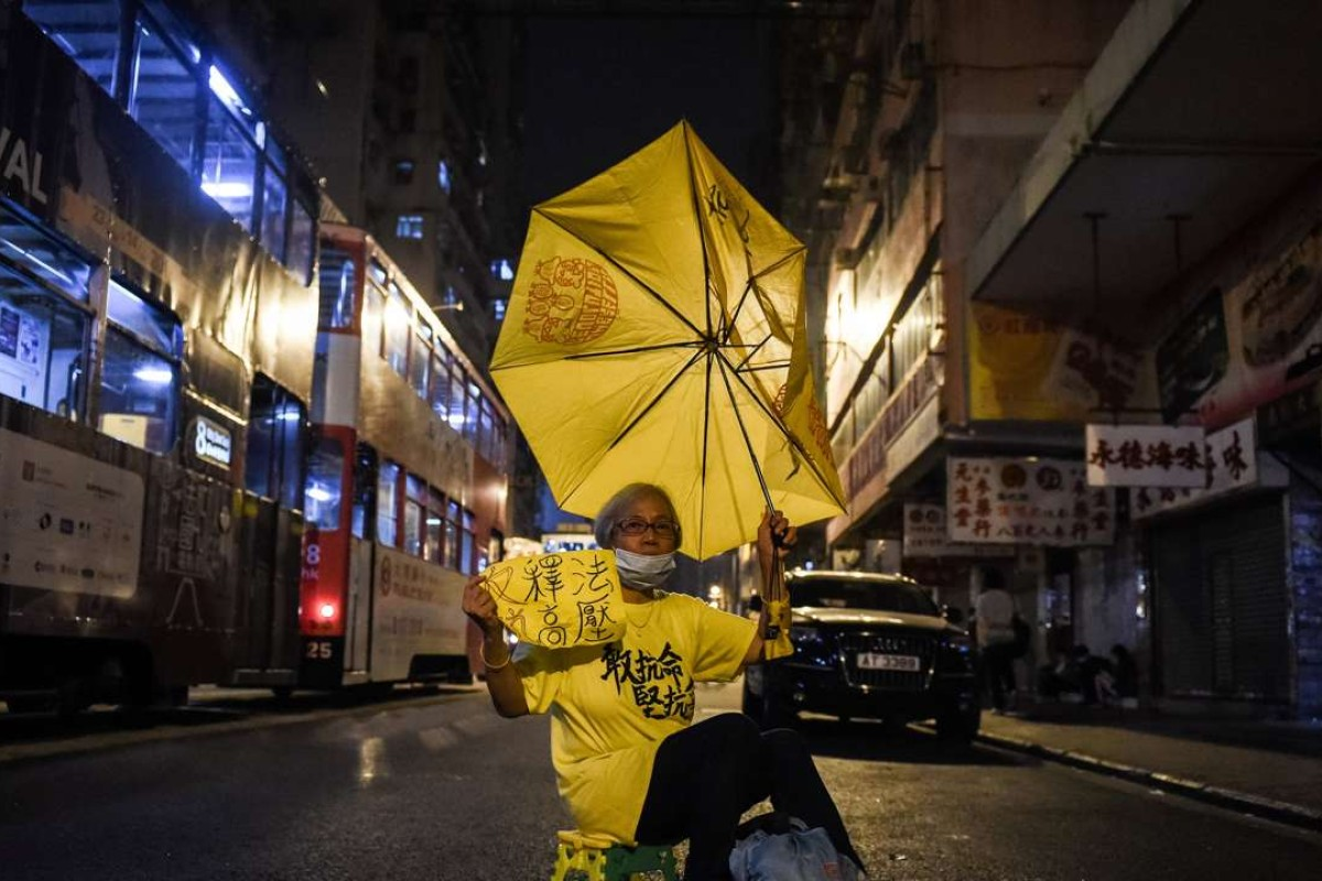 A protestor holds up a yellow umbrella in a street in Hong Kong on November 7, 2016. Hong Kong police used pepper spray November 6 to drive back hundreds of protesters angry at China's decision to intervene in a row over whether two pro-independence lawmakers should be barred from the city's legislature. Photo: AFP