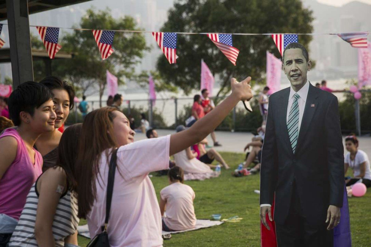 Friends take a selfie with a cardboard cut out of US president Barack Obama in Hong Kong. Photo: AFP