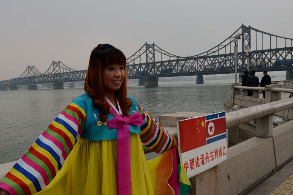 A Chinese woman poses in Korean clothing as trucks carrying Chinese-made goods cross into North Korea on the Sino-Korean Friendship Bridge at the border town of Dandong. Chinese tourism to North Korea is on the increase. Photo: AFP