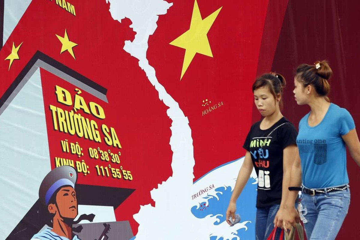 Two women pass a board featuring a map of Vietnam and the words 'Spratly Islands' in a street in Hanoi, Vietnam. Diplomatic disputes between China and Vietnam have prompted resentment of Chinese tourists in the country. Photo: EPA