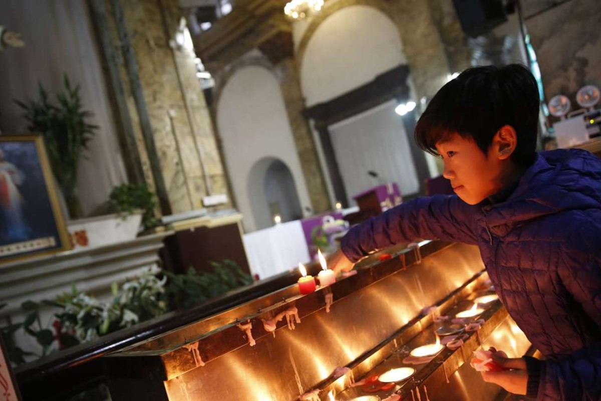 A boy offers candles at a Sunday mass in the state-approved Xuanwumen Catholic Church, otherwise known as the South Cathedral in Beijing. Picture: EPA