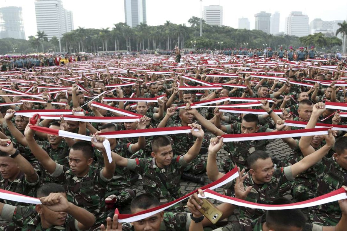 Indonesian soldiers hold up headbands in the colour of the national Red-White flag during a military-sponsored interfaith rally held ahead of a Muslim rally against Jakarta Governor Basuki Tjahaja Purnama. Photo: AP