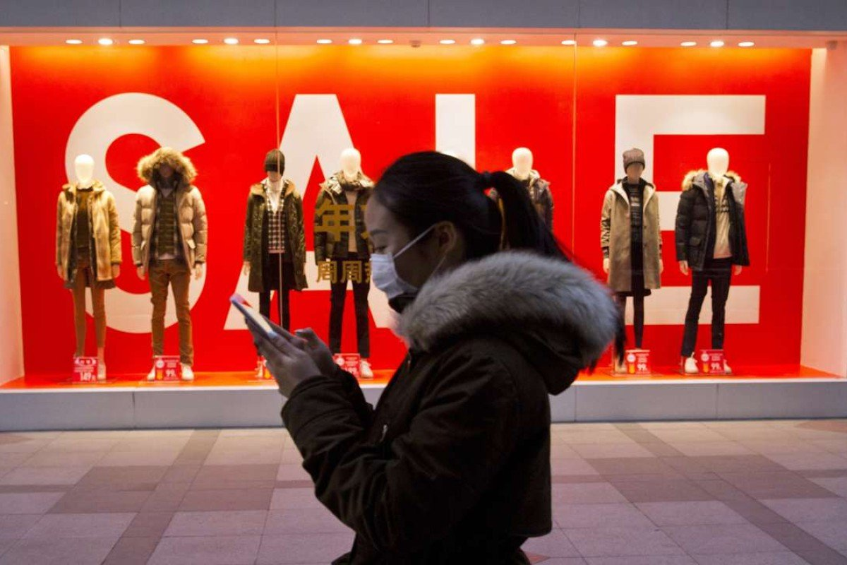 A woman passes mannequins promoting a sale outside a retail outlet in Beijing, China. Photo: AP