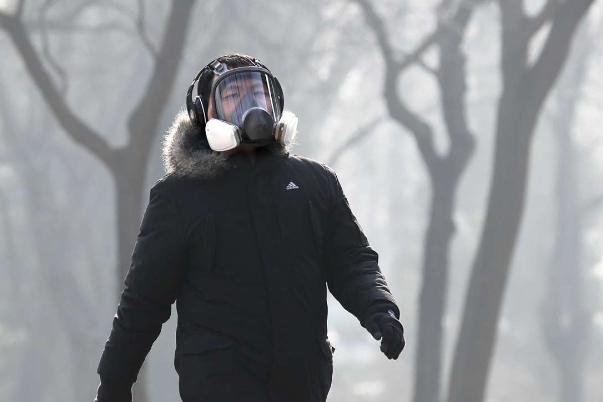 A man walks through Ritan Park in Beijing last week, wearing a full face mask for protection against a toxic smog that descended on the city. Photo: AP