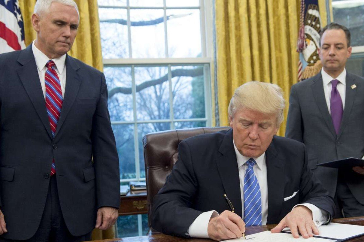 US President Donald Trump signs an executive order withdrawing the US from the Trans-Pacific Partnership. Next to him are US Vice President Mike Pence, left, and White House Chief of Staff Reince Priebus. Photo: AFP