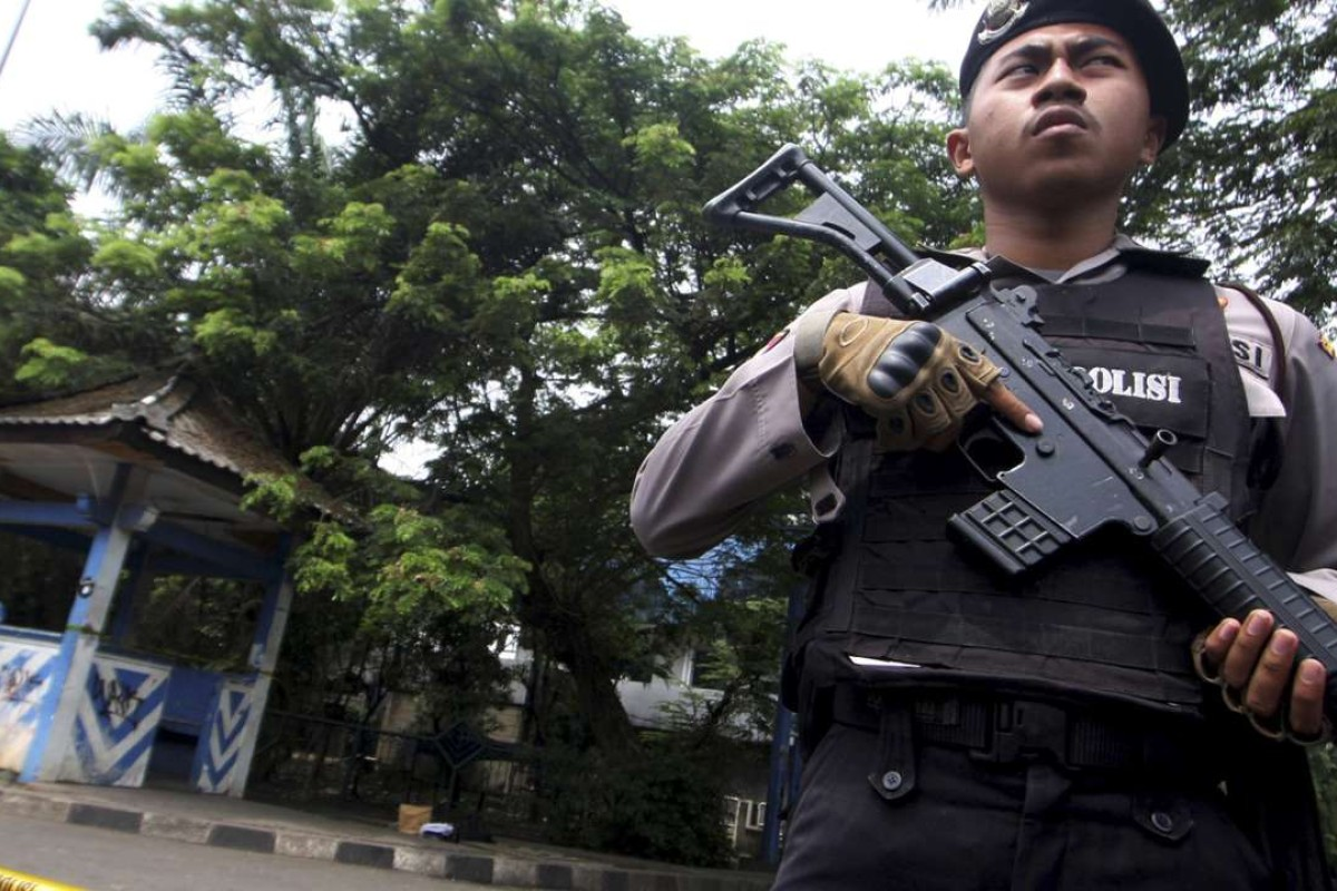 A policeman holds a rifle at a location where a suspected supporter of Islamic State attacked policemen in Tangerang, Indonesia's Banten province. Photo: Reuters.