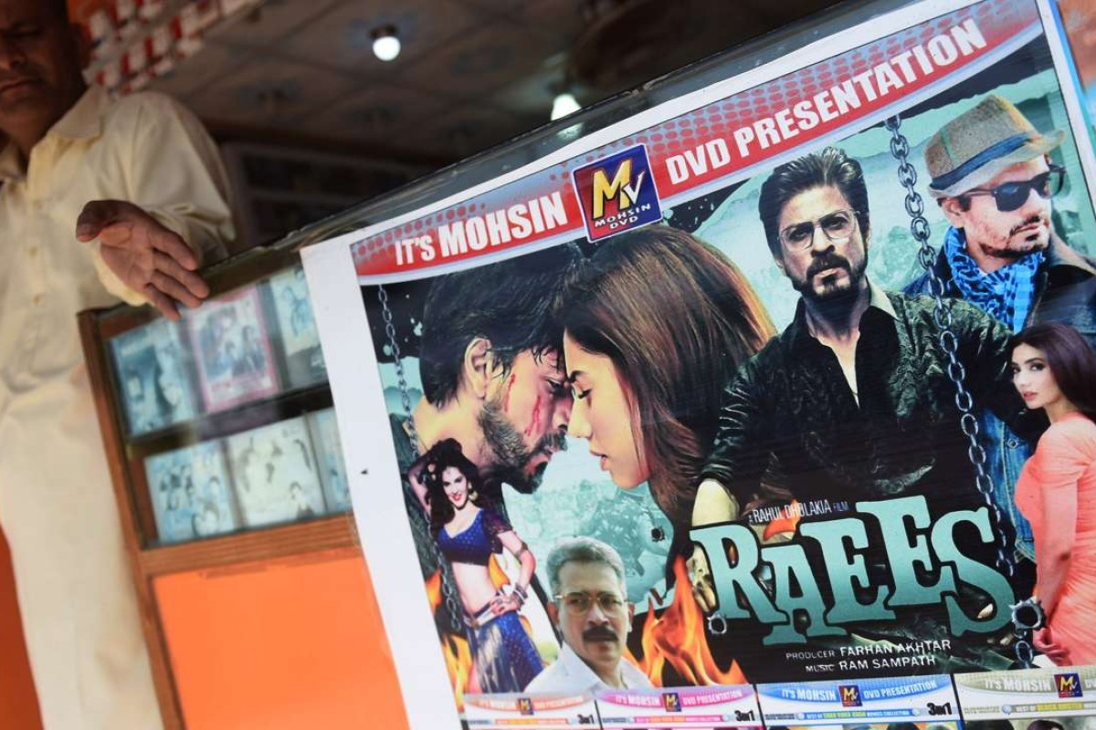 "A Pakistani vendor stands alongside a poster of Indian Bollywood film Raees at his shop in Karachi. Pakistan's ban on the Bollywood thriller sparked a social media backlash after the film was denounced for portraying Muslims as ""terrorists"". Photo: AFP"