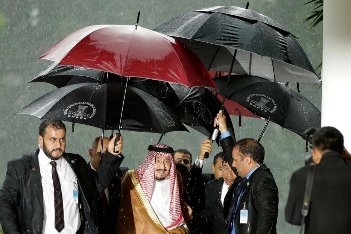 Saudi King Salman is sheltered from the rain upon his arrival at the presidential palace in Bogor, West Java. Photo: AFP