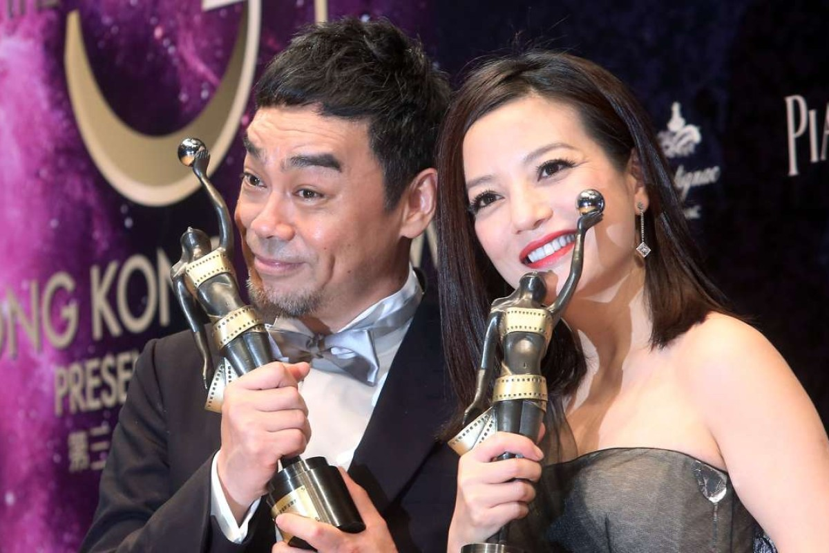 Hong Kong actor Sean Lau (L) holds the best actor award and Chinese actress Zhao Wei holds the Best Actress award pose to photographer at the 34th Hong Kong Film Awards presentation ceremony.