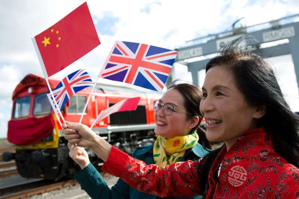 People wave Chinese and Union flags as they pose for photographs during the departure of a freight train transporting containers laden with goods from the UK en route to Yiwu in the eastern Chinese province of Zhejiang. Photo: AFP