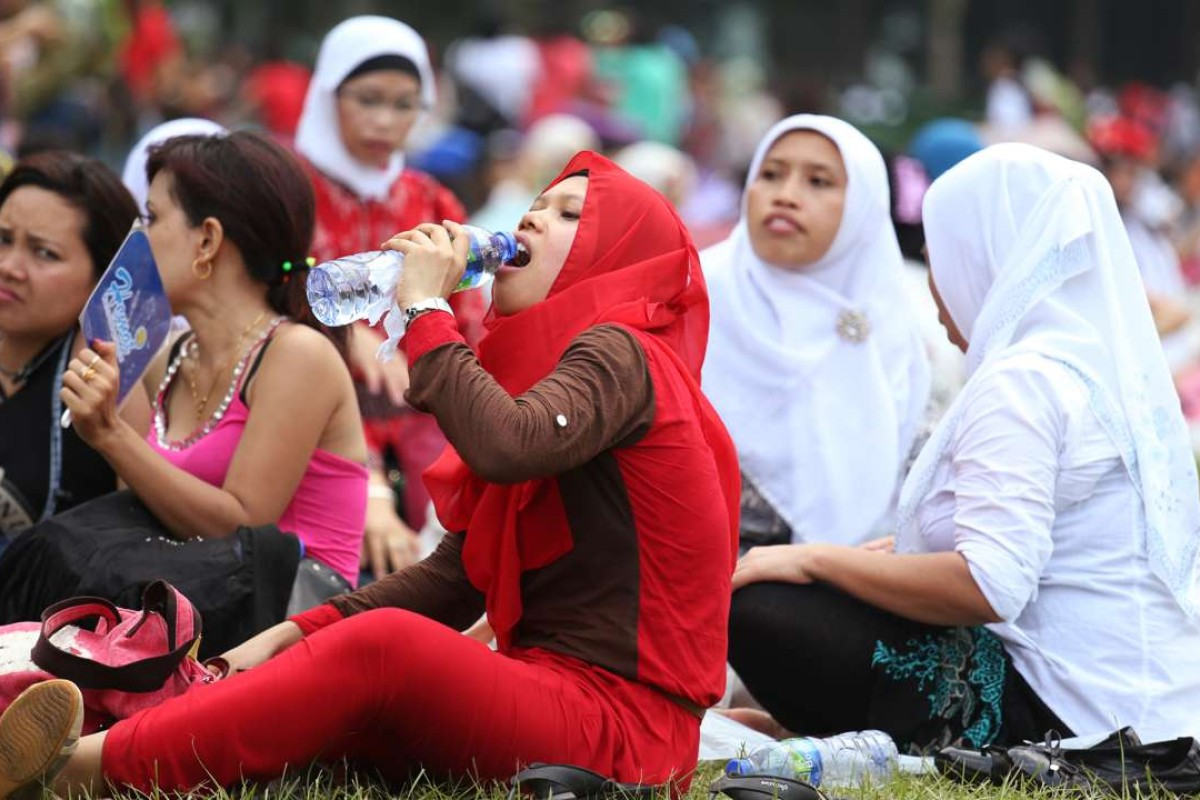Indonesian maids replenish themselves during hot weather at Victoria Park, Causeway Bay. Hong Kong is home to some 350,000 foreign domestic workers, with 156,000 of them coming from Indonesia. Photo: Nora Tam