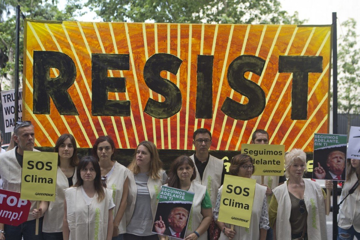 Greenpeace protesters stand in silence with banners outside the US embassy in Madrid, Spain, in protest against President Donald Trump's decision to pull the world's second-largest carbon dioxide emitter out of the Paris Agreement. Photo: AP