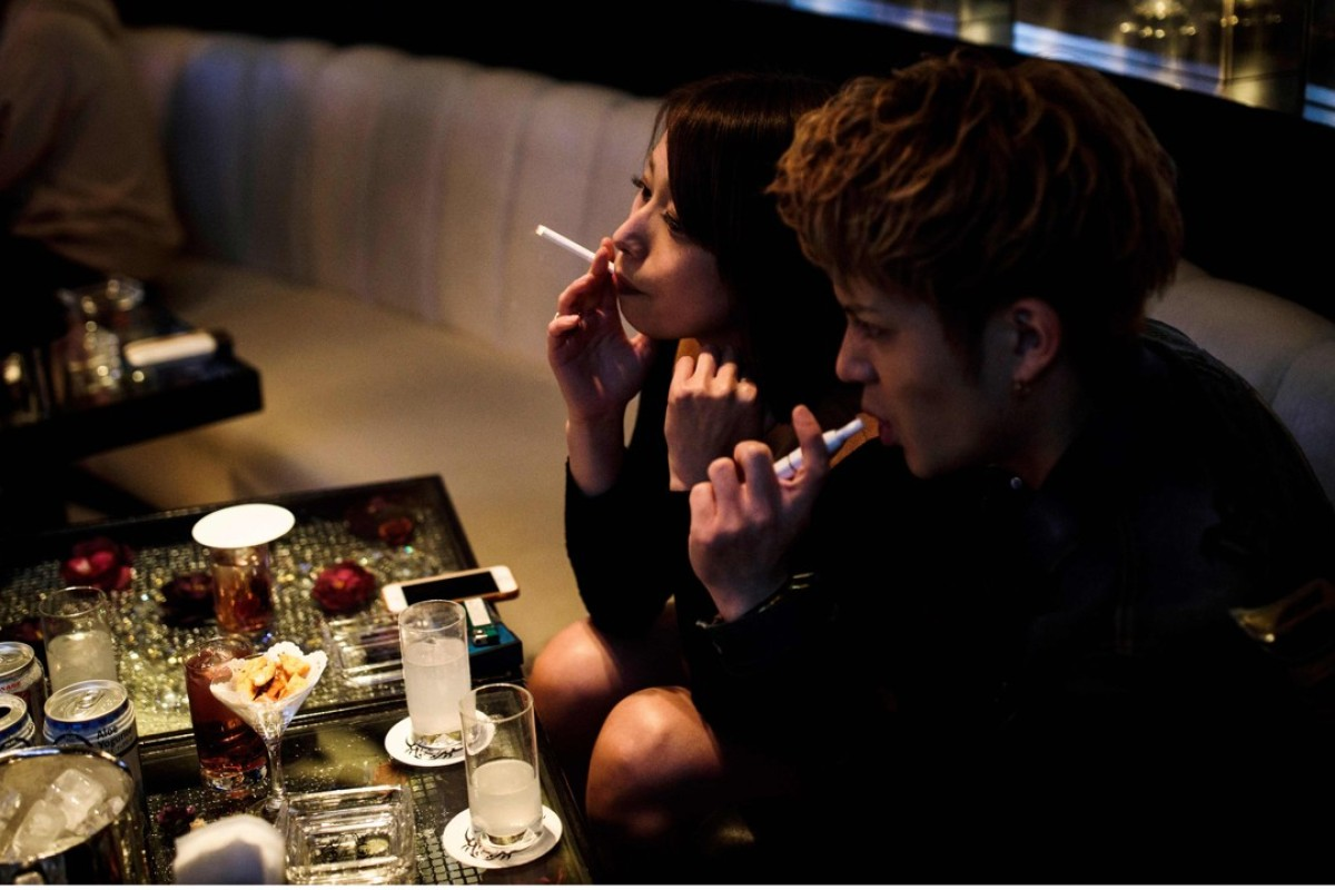 One patron smokes a traditional cigarette while the other uses an electronic version inside a club in the Kabukicho district of Tokyo. The World Health Organisation wants to make Tokyo a 'smoke-free' city in time for the Olympics in 2020. Photo: AFP