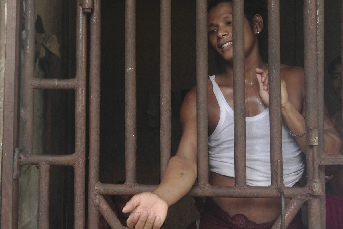 Kyaw Naing, a slave from Myanmar, talks to a security guard through the bars of a cell at the compound of a fishing company in Benjina, Indonesia, in 2014.Photo: AP
