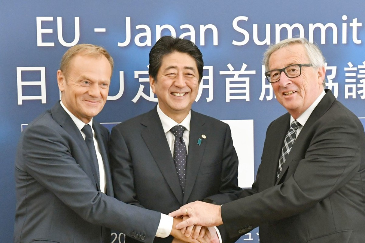 From left, European Council President Donald Tusk, Japanese Prime Minister Shinzo Abe and European Commission President Jean-Claude Junker shake hands in Brussels. Photo: Kyodo