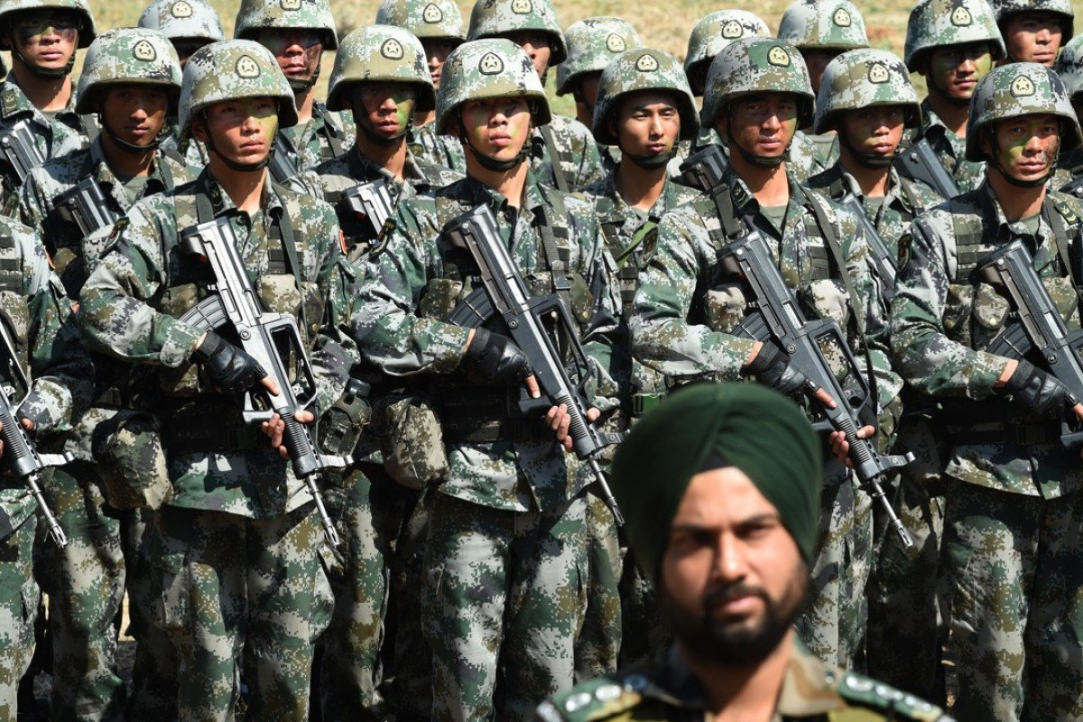 An Indian Army soldier stands in front of a group of People's Liberation Army (PLA) soldiers as they line up after participating in an anti-terror drill. Photo: AFP