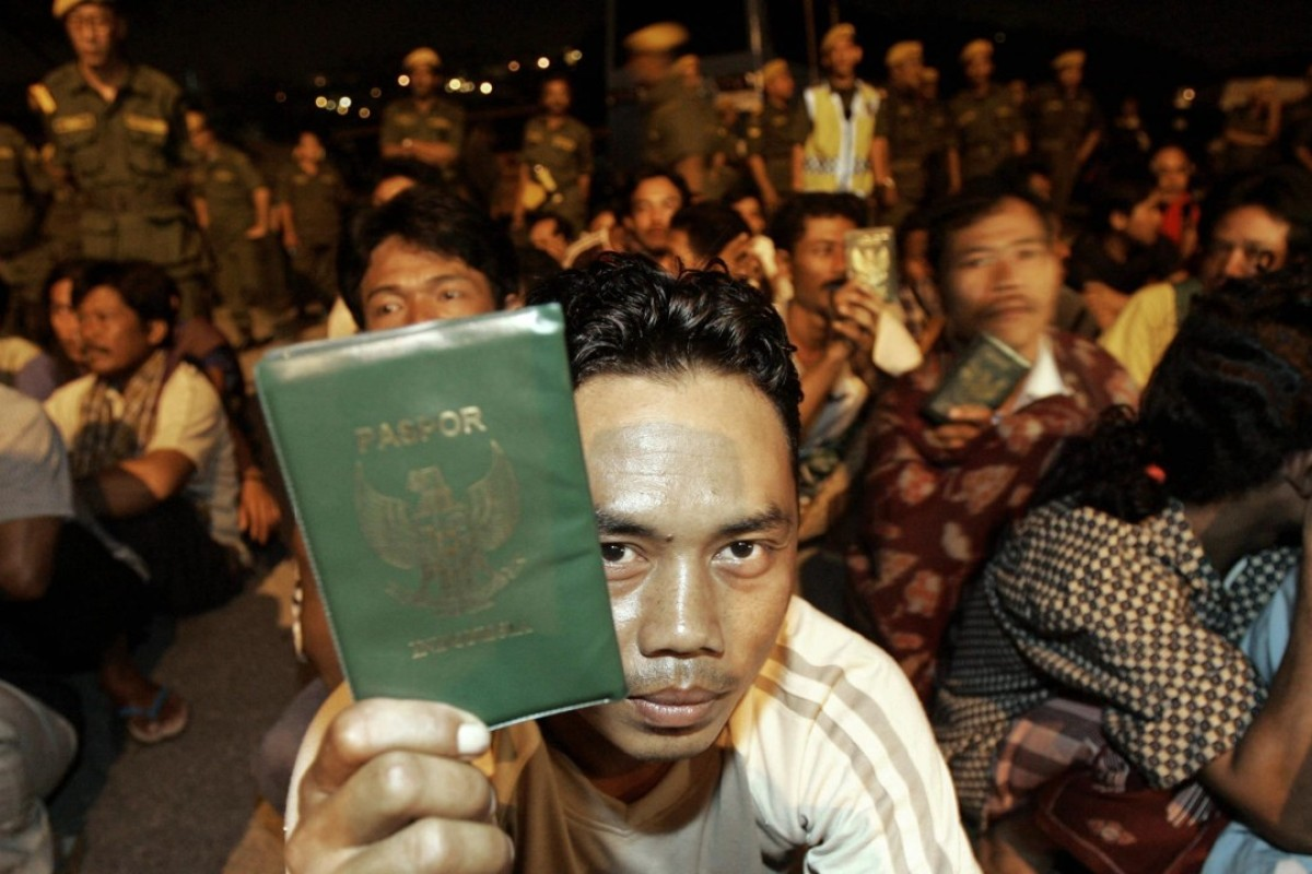 An Indonesian migrant worker in Kuala Lumpur shows his passport during a late-night immigration raid. Photo: AFP