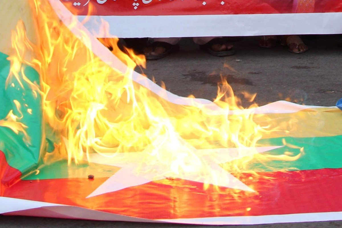 A Myanmar flag is torched in Pakistan during a protest in support of Rohingya Muslims. Photo: AFP