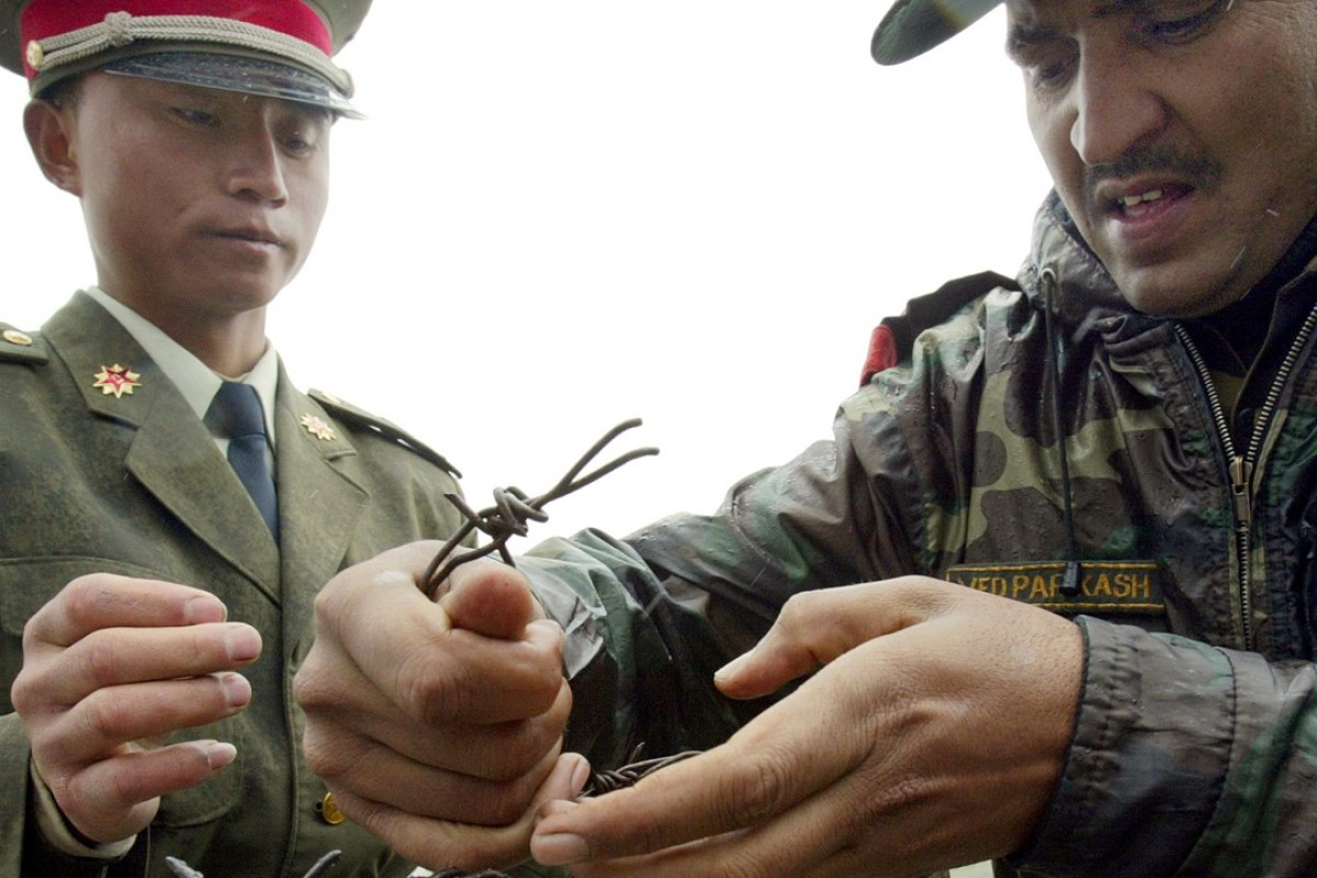 A Chinese soldier and his Indian counterpart erect a barbed wire fence at the Nathula border crossing between India and China, in July 2006. Picture: AFP