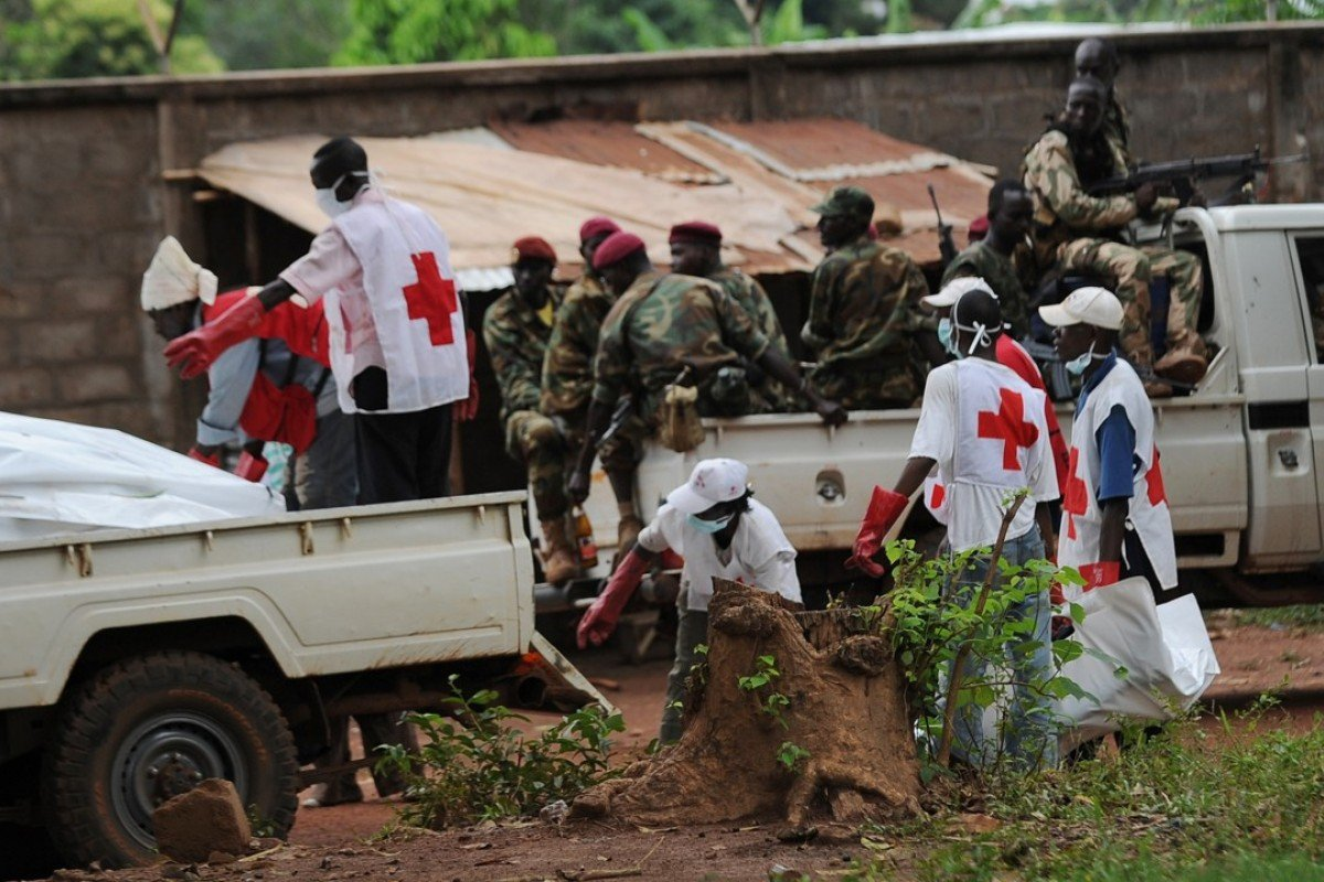 Red Cross workers retrieve bodies from the site of clashes in Bangui, in the Central African Republic, as rebels look on from a pickup truck, in 2013. Picture: AFP