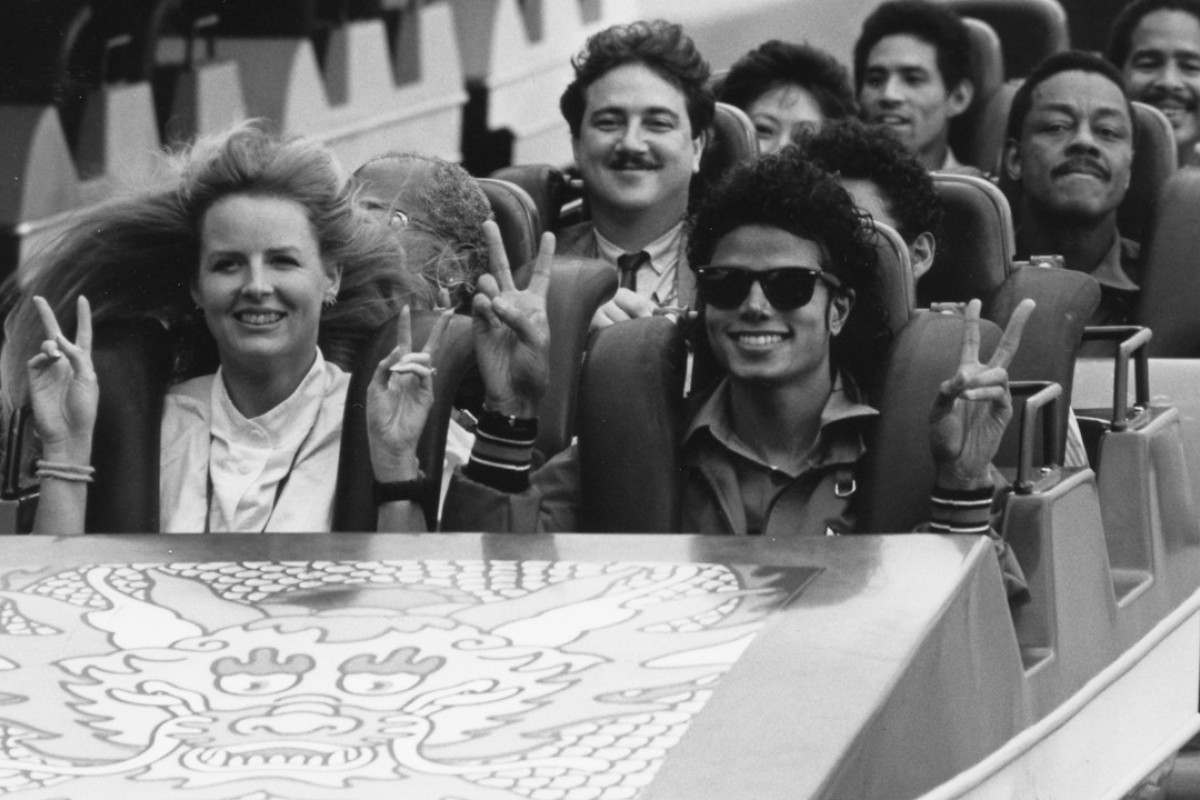 Michael Jackson, his minders and other visitors taking a roller coaster ride at Ocean Park. Entertainer Dr Penguin (with moustache) sits behind him.