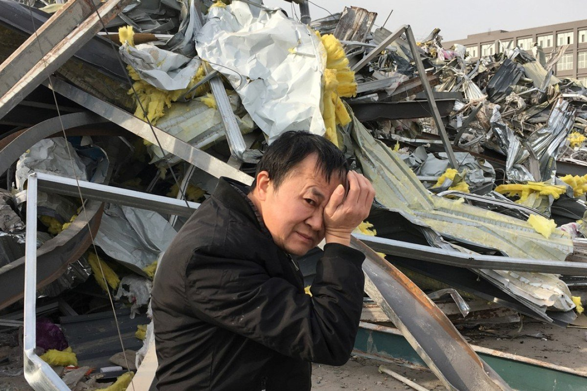 A migrant worker walks past buildings demolished following a citywide fire safety inspection in Daxing district, Beijing. Photo: Reuters