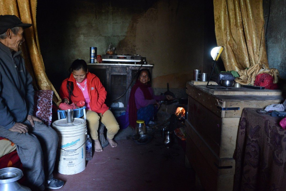 Pratima Sherpa (second from left) is watched by her parents as she does household chores at their home in Kathmandu. Pictures: AFP