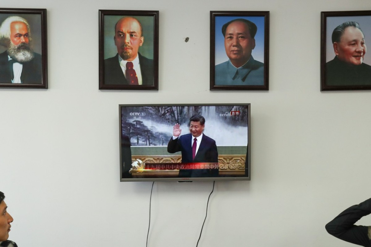 Framed portraits of German philosopher Karl Marx Soviet state founder Vladimir Lenin and China's late leaders Mao Zedong and Deng Xiaoping hang above a screen showing President Xi Jinping