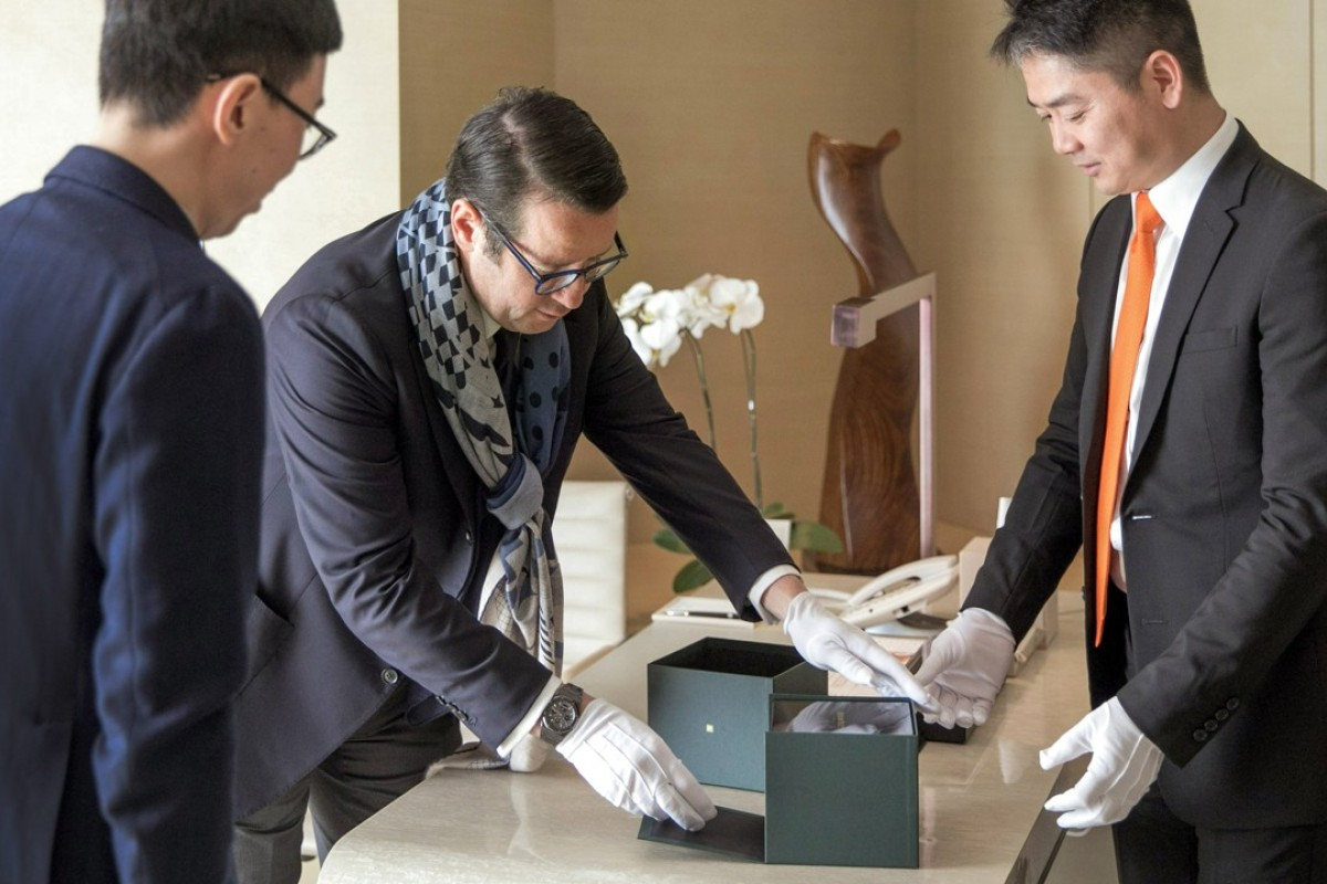 Audemars Piguet CEO François-Henry Bennahmias (centre) and Richard Liu, founder of JD.com (right), deliver a luxury Audemars Piguet watch to the Beijing collector, which was bought on WeChat.
