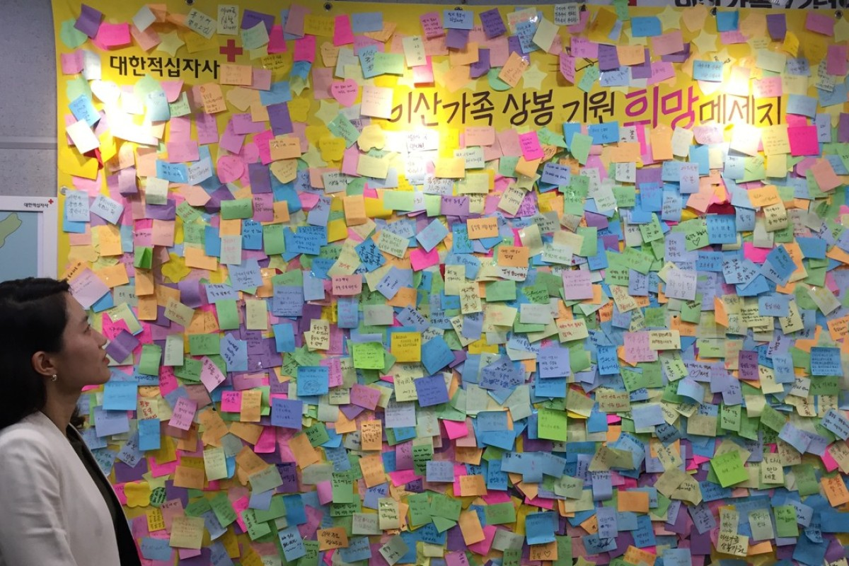 Jung Ja-eun, head of the inter-Korean cooperation team at the Korean Red Cross, looks at a wall of notes left behind by international visitors and separated families inside the organisation's video reunion room. Photo: Crystal Tai