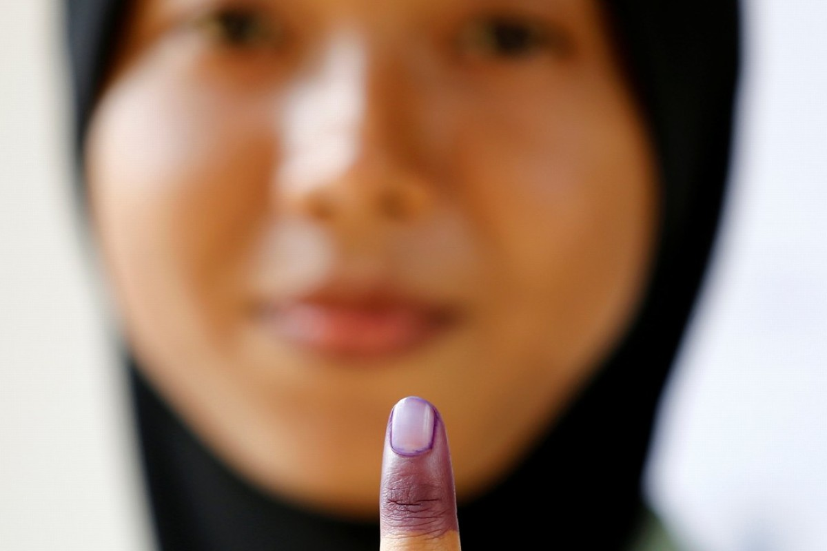 A Malaysian military officer shows her finger marked with indelible ink after casting her ballot during the early voting at Kementah Camp in Kuala Lumpur. Photo: Reuters