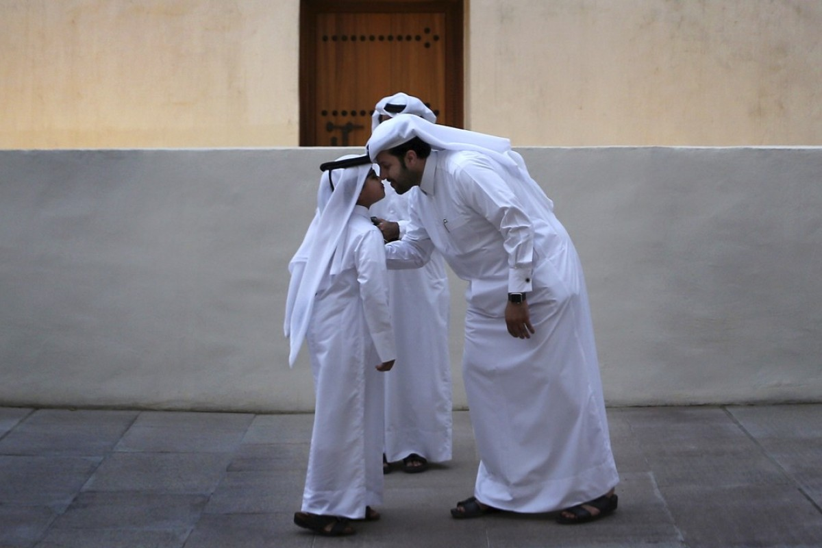 A man greets a boy in traditional Gulf Arab style in Doha, Qatar. Photo: AP