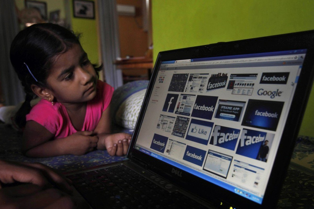 An Indian works on a laptop as a child watches in Hyderabad, India. Photo: AP