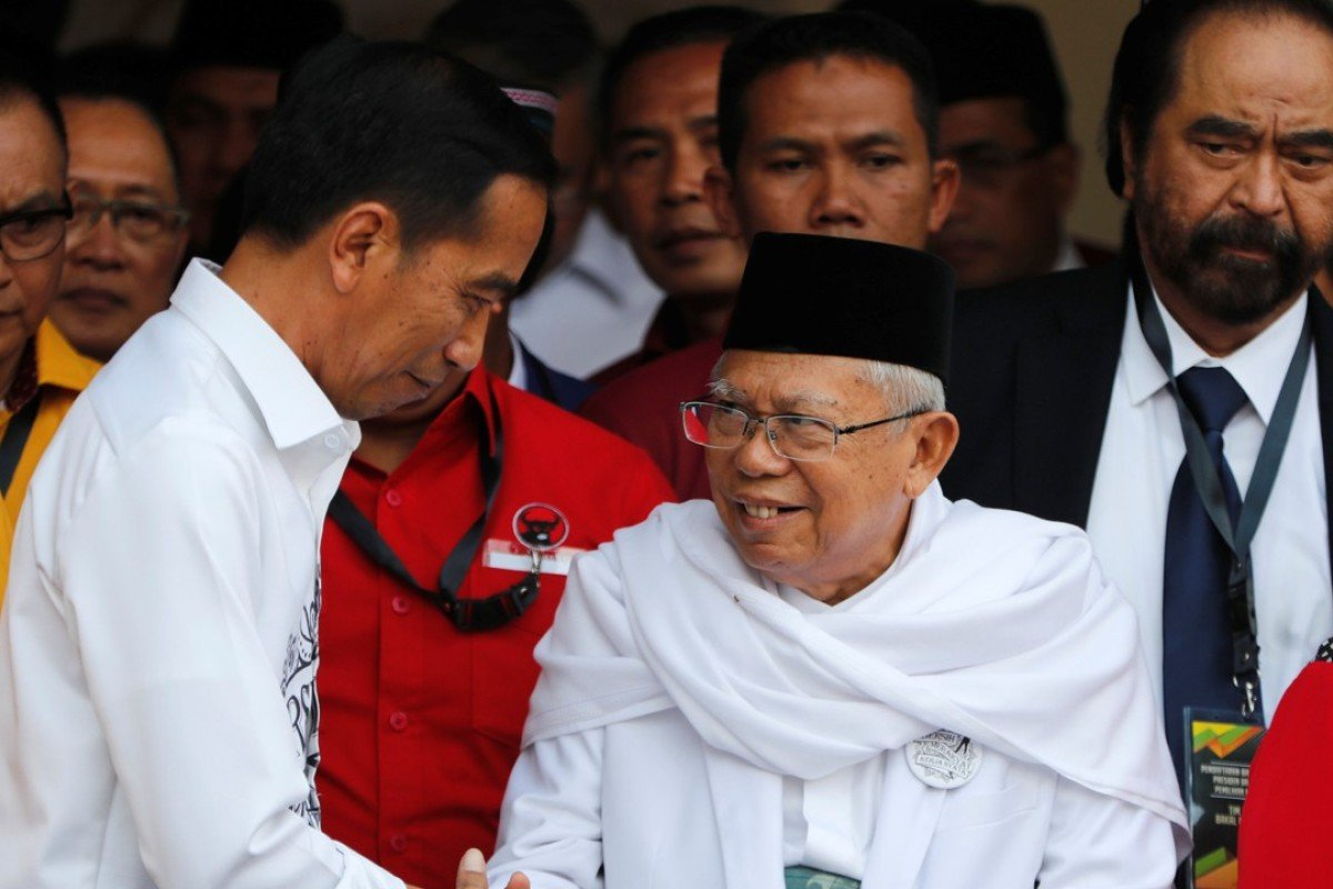 Indonesian President Joko Widodo, left, with his vice-presidential running mate Ma'ruf Amin while greeting supporters in Jakarta on Friday. Photo: Reuters