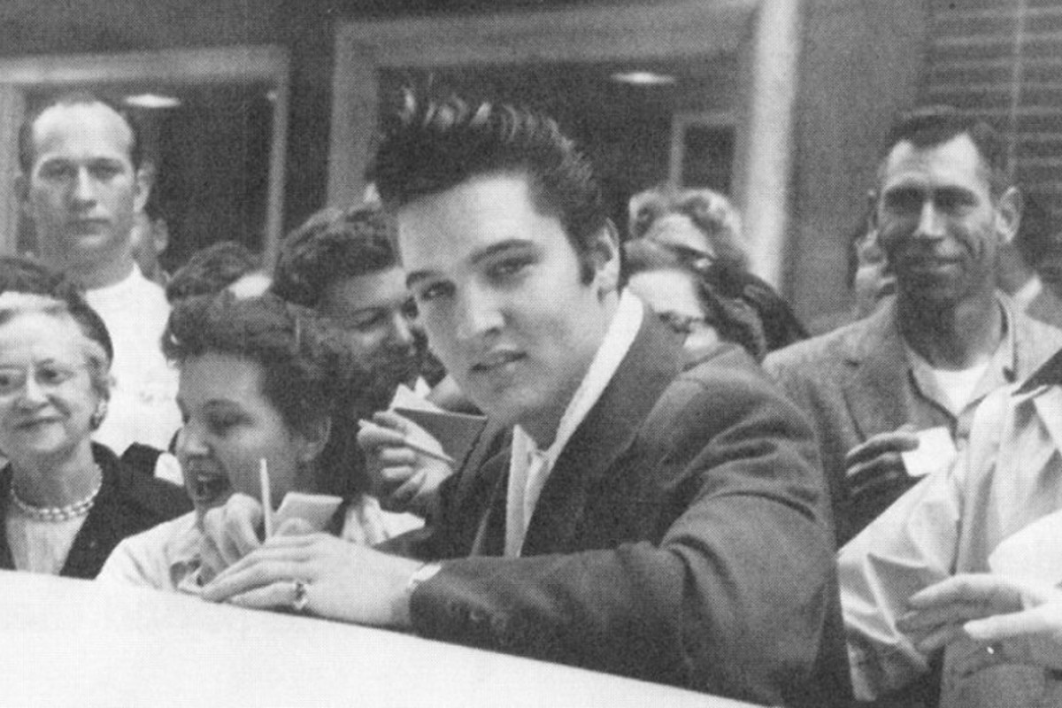 A young Elvis Presley – who died 41 years ago on August 16 – signs autographs for a crowd of fans after being spotted while out in Memphis, the United States, on December 11, 1956.
