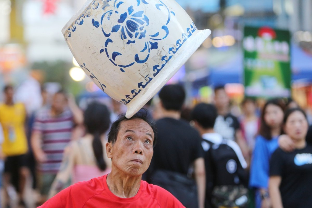 A street performer in Mong Kok, in Hong Kong, before the pedestrian zone was reopened to vehicles, forcing the entertainers out. Picture: Winson Wong